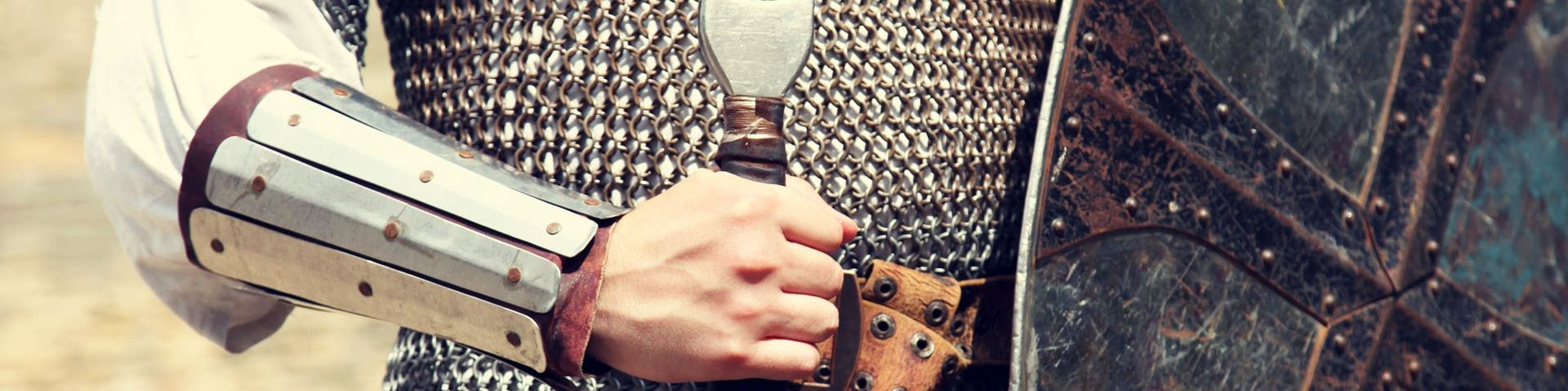 A knight's chain-mailed torso and arm, with the handle of a sword and partial shield showing.